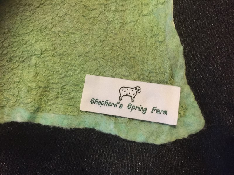 label close on pale green scarf